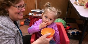 Therapist helps child feed herself