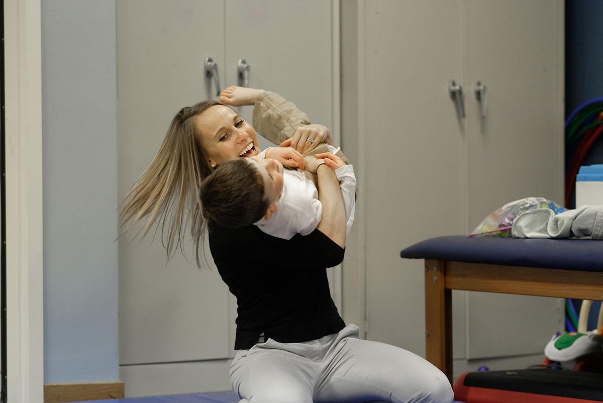 Therapist hugging autistic child