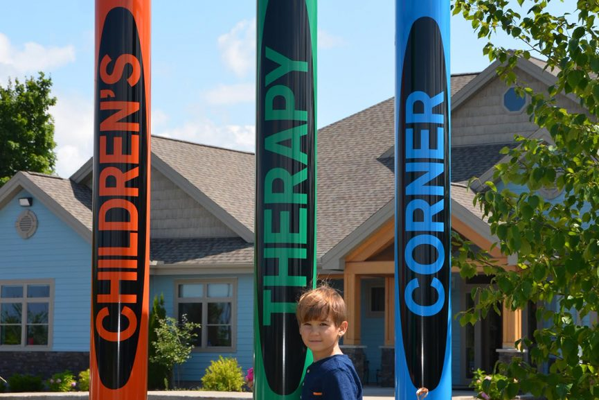 Child standing in front of crayon structure at Children's Therapy Corner in Midland